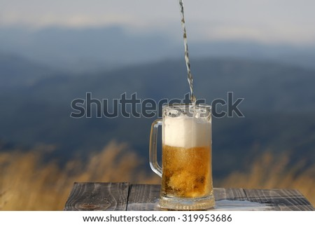 One glass mug pouring with lager or porter delicious frothy beer on wooden table top sunny day outdoor on natural with mountain hills and yellow dry grass background, horizontal picture - stock photo