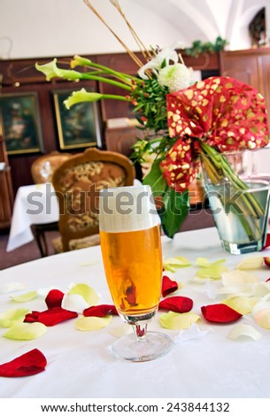 One glass of beer on the table covered by flower petals in restaurant. - stock photo
