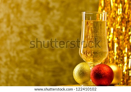 One glass of champagne with a Christmas decor in the background. very shallow depth of field, focus on near glass. - stock photo