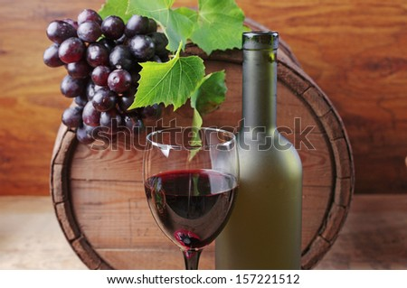 One glass of red wine, one bottle, grapes and oak barrel.  Wooden background