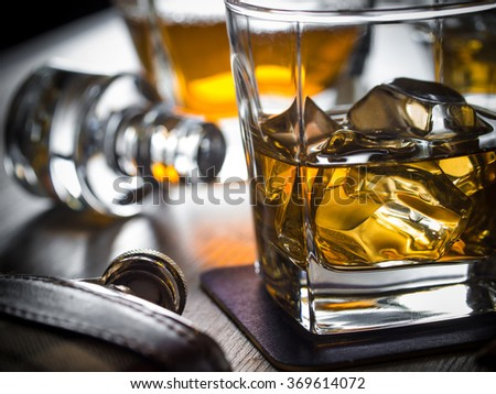 One glass of whiskey on the rocks on a wooden table
