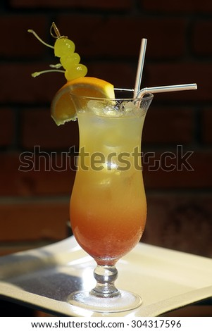 One glass with alcoholic sex on beach cocktail of vodka peach liqueur cranberry water orange juice and slice with green grapes and drink straws on white plate on brick wall background, vertical photo - stock photo