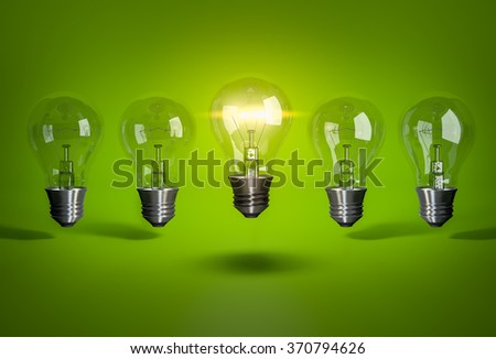 One glowing bulb in row of light bulb on green background - stock photo