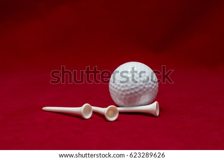 One golf ball and three pin and red flannel background