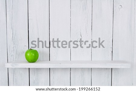 One green apple on a shelf. A wooden, white background. - stock photo