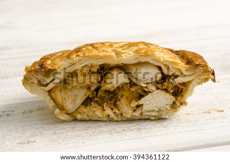 One half of a delicious golden brown chicken pie on a white wooden background. - stock photo