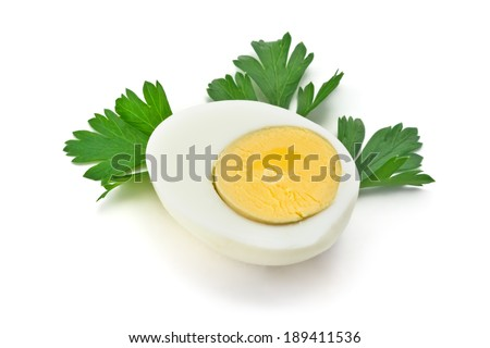 one half of boiled egg with parsley leaves on a white background - stock photo