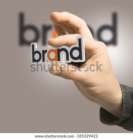 One hand holding the word brand over a beige background. Branding concept. The image is a composition between 2D illustration, 3D rendering and photography - stock photo