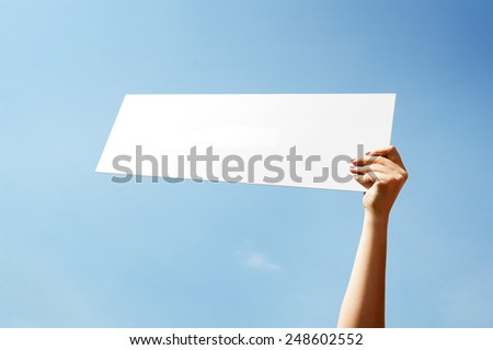 One hand holds white sheet on background of blue sky