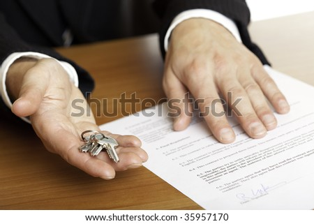 one hand of businessman gives  house keys to the hand of another businessman. Signed contract and pen visible in background. - stock photo
