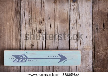 One hand painted arrow on a wooden plank on a rough wooden background - stock photo