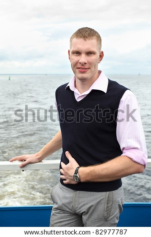 One handsome Caucasian man standing on deck of yacht