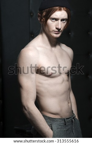 One handsome red haired young stylish unshaven man in hat and grey trousers with naked torso having beautiful sexy muscular body standing in studio on black leather background, vertical picture - stock photo