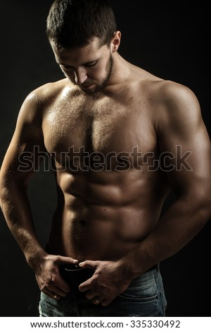 One handsome sexual strong young man with muscular body in blue jeans holding hands on torso standing in studio on black background, vertical picture - stock photo