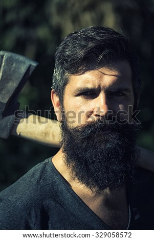 One handsome strong stylish male logger of young man with long lush black beard and moustache in shirt holding wooden axe standing in forest outdoor on natural background, vertical picture - stock photo