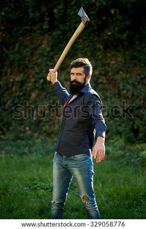 One handsome strong stylish male logger of young man with long lush black beard and moustache in shirt holding wooden axe standing near wall with climber plant outdoor, vertical picture - stock photo
