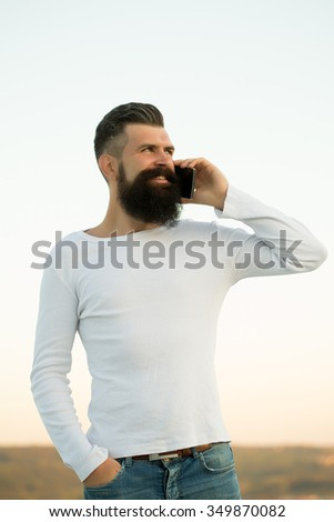 One handsome young bearded smiling business man in white sweater holding and speaking on cell phone outdoor on light sky natural background, vertical picture - stock photo