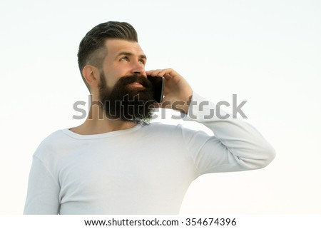One handsome young bearded smiling business man in white sweater holding and speaking on cell phone outdoor on light sky natural background, horizontal picture - stock photo