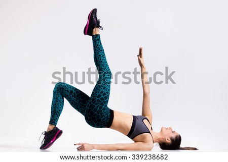 One happy attractive gorgeous young fit modern woman in aquamarine sportswear with ponytail working out, dancing, full length, studio image on gray background - stock photo