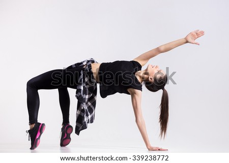 One happy attractive gorgeous young fit modern woman with ponytail working out in sportswear and plaid shirt, dancing, doing backbend, bridge exercise, full length, studio image on gray background - stock photo