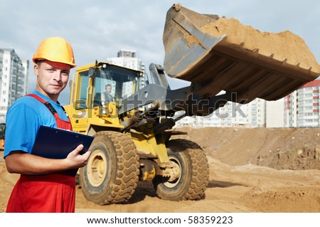 One happy builder worker with clipboard inspecting earthmoving works at construction site - stock photo