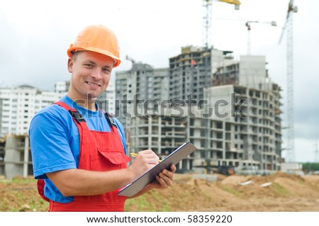 One happy builder worker with clipboard inspecting works at construction site - stock photo