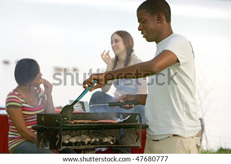 one happy twenties African American male cooking on a bbq grill outdoors in a park with two friends behind - stock photo