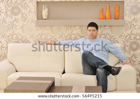one happy young man relax at home in livingroom with modern style furniture indoor - stock photo
