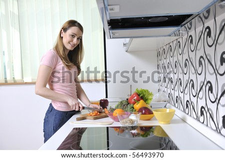 one happy young  woman with apple in kitchen and other food and vegetables - stock photo