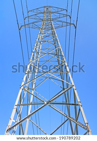 One high voltage electrical power transmission line tower.Front low angle perspective view.Steel lattice pylon structure.Sharp pointed spikes on legs,diagonal bars as climbing deterrent.Blue sky.