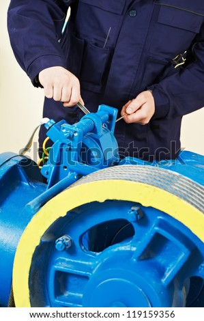 One hoist lift worker fitting fixing and tuning elevator brakes mechanism - stock photo