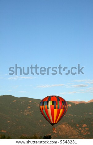 One hot air balloon during early morning ascend. Mountains in background - stock photo
