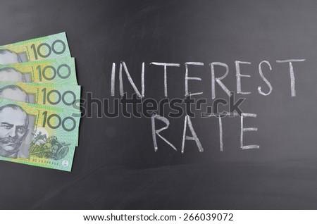 One hundred Australian dollar bills on a blackboard where interest rate is written in chalk - stock photo