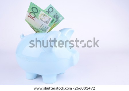 One hundred Australian dollar notes inserted into a blue piggy bank - stock photo