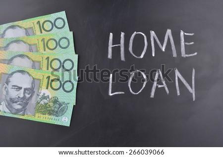 One hundred Australian dollar notes on a blackboard where home loan is written in chalk - stock photo