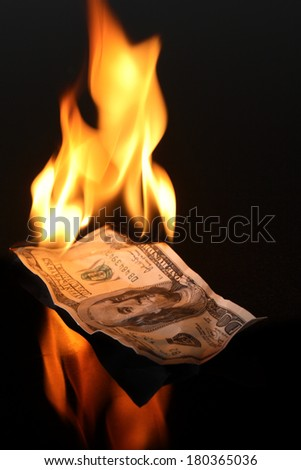 One hundred dollar bill on fire with black background - stock photo