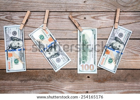 One hundred dollar bills hanging on a clothes pins - stock photo