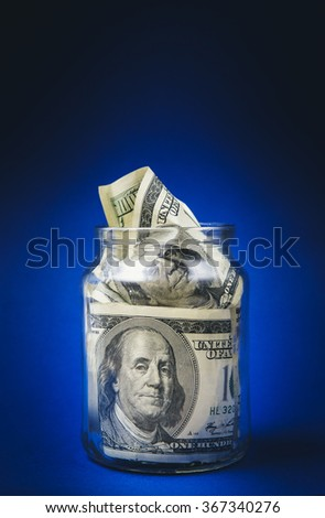 One hundred dollar bills in a glass jar. Blue background - stock photo