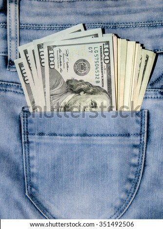 one hundred dollar bills in the pocket of blue jeans - stock photo