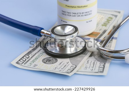 One hundred dollar bills with stethoscope and prescription bottle. - stock photo