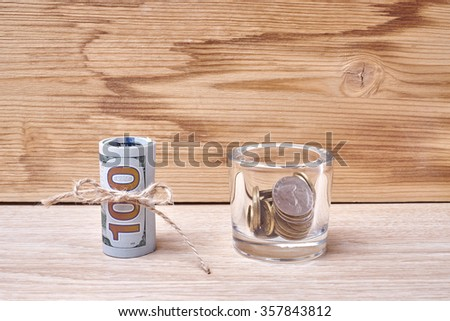 one hundred dollars and cents on a wooden table - stock photo