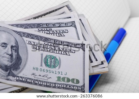 One hundred dollars banknotes and notebook closeup - stock photo