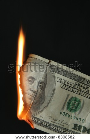 One hundred dollars bill on fire over black background