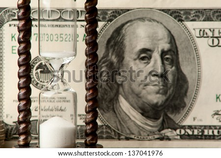One hundred dollars note with hourglass. Studio shot. - stock photo