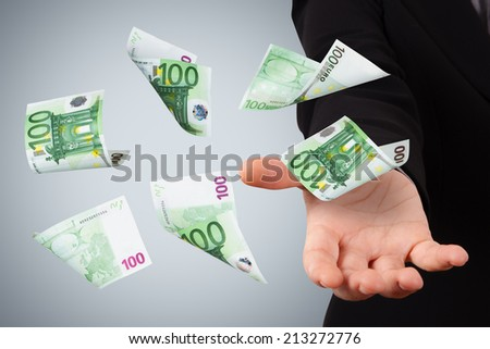 One hundred euro money banknotes flying and falling on young business woman hand.