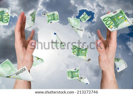 One hundred euro money banknotes flying and falling on young male hands on cloudy background. - stock photo