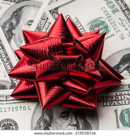 One hundred US dollars bills with red holidays bow - stock photo
