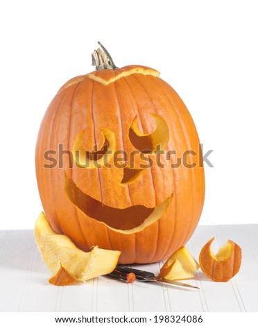 One Large Pumpkin carved and ready for candlelight on white background and on a table.  A trick or treat display - stock photo