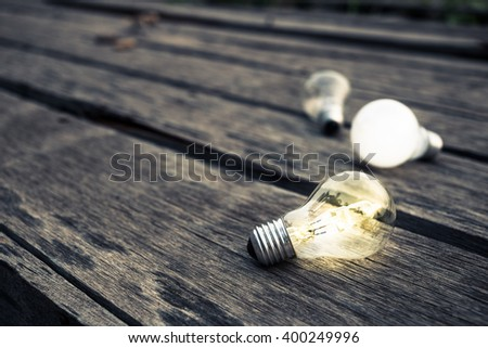 One light bulb glowing among the others - stock photo