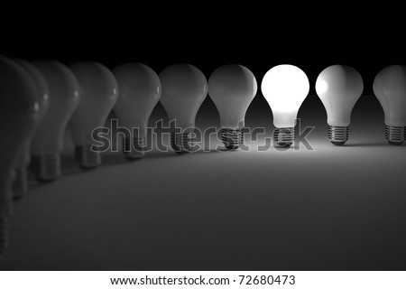 One lit light bulb amongst other broken light bulbs - stock photo